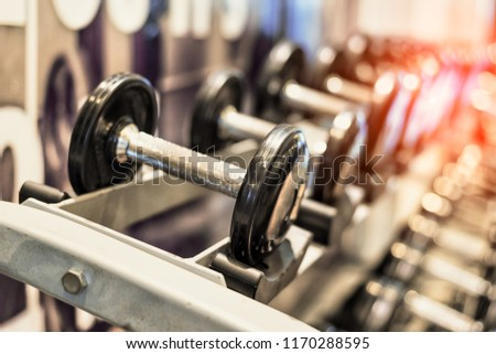 Close up of black metallic steel dumbbell set. Dumbbells on rack in sport fitness center. Workout training and fitness gym concept. Healthy and well being concept. Sport equipment and tool theme.  #1170288595