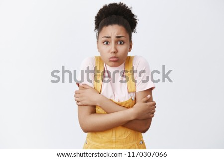 It is getting chilly, lend me coat. Portrait of cute timid dark-skinned girlfriend in summer yellow overalls, hugging herself and trembling, shaking from cold wind, freezing on evening night #1170307066