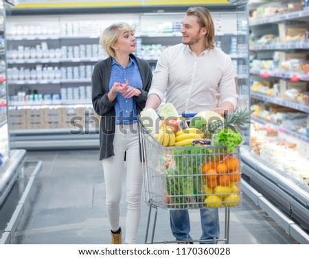 Positive family customers with full trolley of healthy organic vegetables and fruits in grocery store during weekly food shopping #1170360028