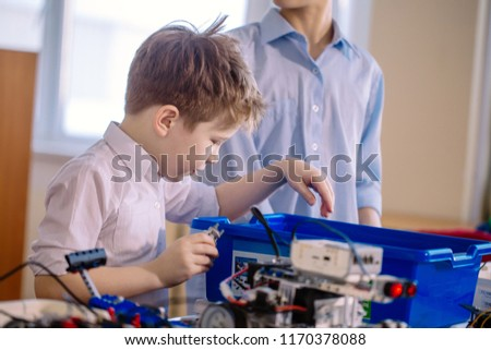 Fair haired cheerful little boy making a robot from metal parts and microcircuits, his brother helps him, close up. Happy emotion and enjoyment. #1170378088