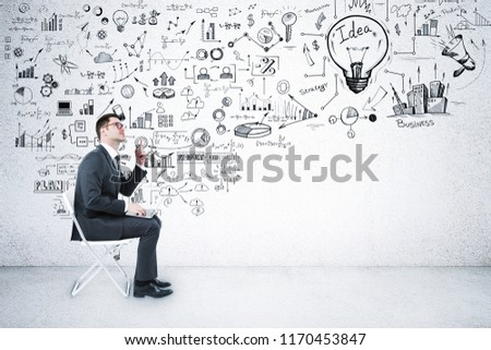 Side view of young businessman sitting on chair in interior with business sketch. Success and computer concept  #1170453847