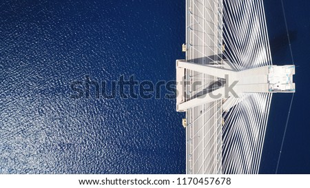 Aerial bird's eye drone photo of state of the art suspension bridge crossing over deep blue sea #1170457678