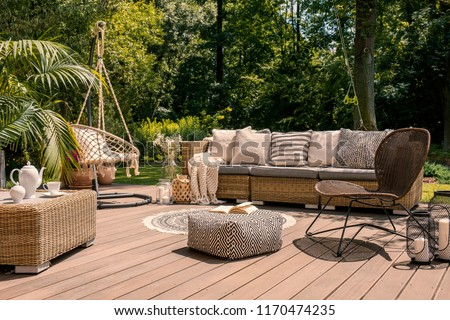 A rattan patio set including a sofa, a table and a chair on a wooden deck in the sunny garden. #1170474235