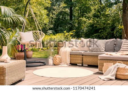 A big terrace with a comfortable leisure sofa with cushions, a table and a string swing in a green garden during sunny vacation. #1170474241
