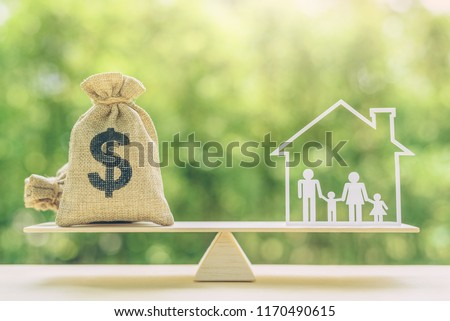 Cost of living, home loan, family finance and child trust fund concept : US dollar bags, family members live inside a house on basic balance scale, depicts the expenditure a family should prepare for #1170490615