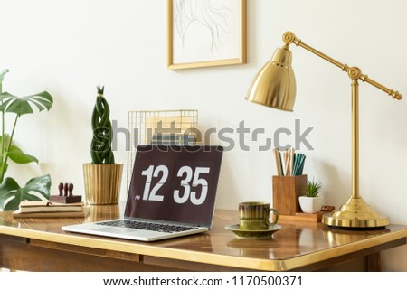 Gold lamp, laptop and plant on wooden desk in white freelancer's interior with poster. Real photo #1170500371