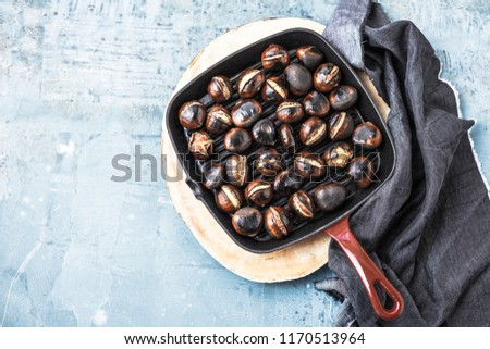 Roasted chestnuts served in chestnut pan on an old table  #1170513964