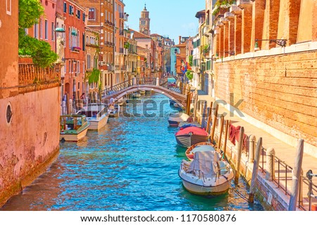 Perspective of a canal with moored motorboats in Venice on sunny summer day, Italy                               #1170580876