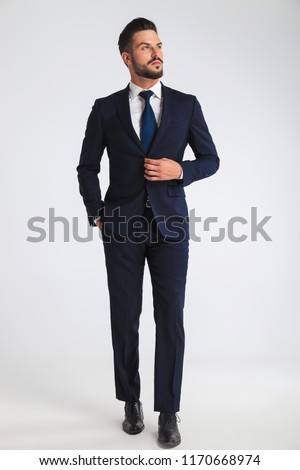 handsome businessman walking on light grey background with hand in pocket looks up to side, full length picture