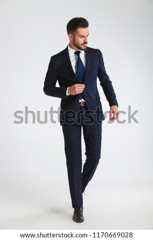 young businessman walking on light grey background and buttoning his navy suit while looking down to side, full body picture #1170669028