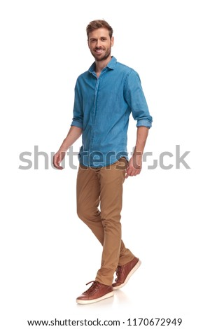 side view of a laughing young casual man walking on white background #1170672949