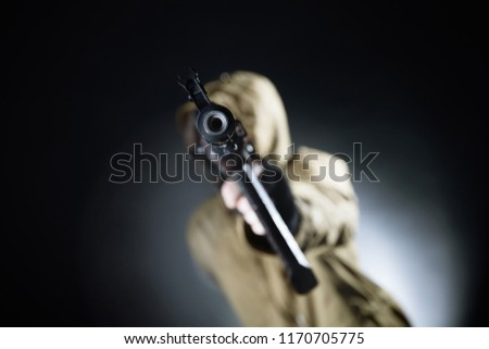 Dangerous armed terrorist with mask and machine gun on dark background. Concept of terrorism and violence. #1170705775