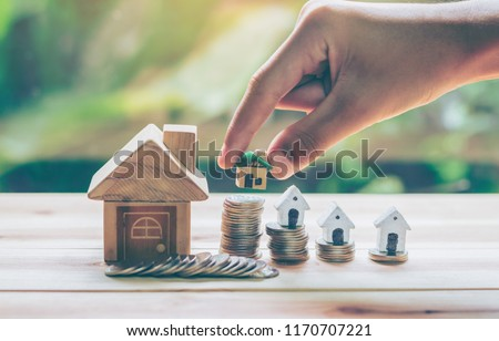 House placed on coins Men's hand is planning savings money of coins to buy a home concept concept for property ladder, mortgage and real estate investment. for saving or investment for a house, #1170707221