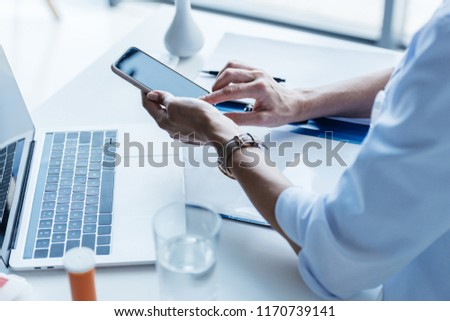 partial view of female doctor using smartphone at table with laptop in office  #1170739141