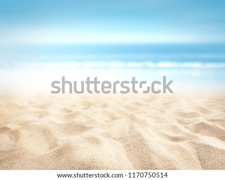 Bumpy tropical sandy beach with blurry blue ocean and sky