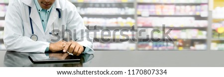 Male pharmacist sitting at table with tablet computer in pharmacy office. Medical healthcare staff and drugstore business. Royalty-Free Stock Photo #1170807334