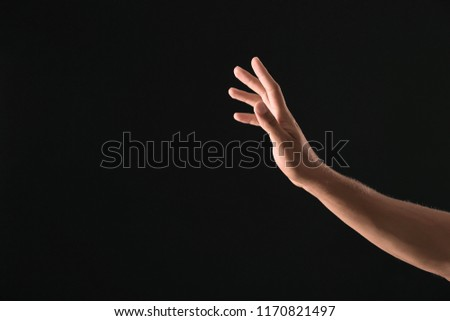 Young man using virtual screen on dark background #1170821497