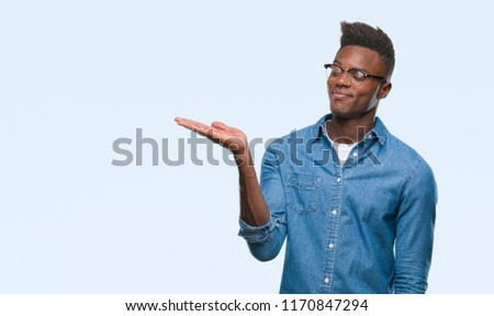 Young african american man over isolated background smiling cheerful presenting and pointing with palm of hand looking at the camera. #1170847294