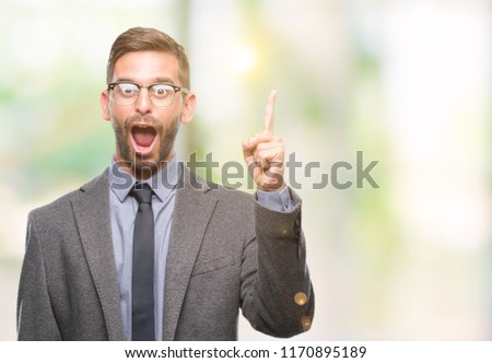 Young handsome business man over isolated background pointing finger up with successful idea. Exited and happy. Number one. #1170895189