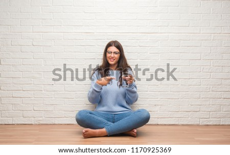 Young brunette woman sitting on the floor drinking glass of water very happy pointing with hand and finger #1170925369