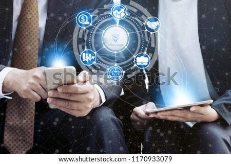 Ethereum and cryptocurrency investing concept - Businessman using mobile phone application to trade Ethereum ETH with another trader in modern graphic interface. Blockchain and financial technology. #1170933079