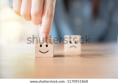 Close up customer hand choose smiley face and blurred sad face icon on wood cube, Service rating, satisfaction concept. #1170951868