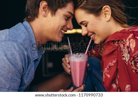Close up of a happy couple sharing a milkshake with two straws. Smiling man and woman on a date sitting at a restaurant sharing a milkshake. #1170990733