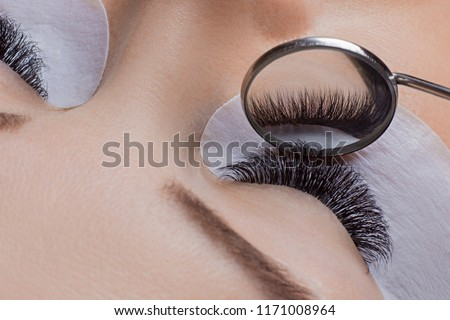 Woman eye with beauty lashes. Eyelash extension procedure. Royalty-Free Stock Photo #1171008964