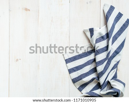 View from above on white wooden table with linen kitchen towel or textile napkin. Blue tablecloth on white wood tabletop. Copy space for text. Can use as mock up for design. #1171010905