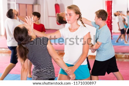 Adult and teen people practicing self defence technique in pairs at gym Royalty-Free Stock Photo #1171030897