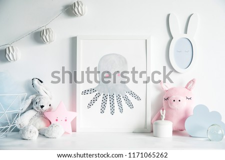 Stylish scandinavian nursery interior with mock up photo frame , white rabbit, pinky pig  and star. Hanging cotton lamps and mirror on the  white background wall.