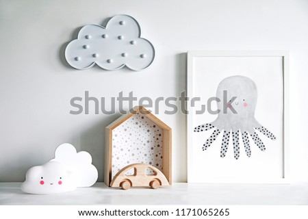 The modern sandinavian newborn baby room with mock up poster frame, wooden car and clouds. Minimalistic and cozy interior with white walls. #1171065265