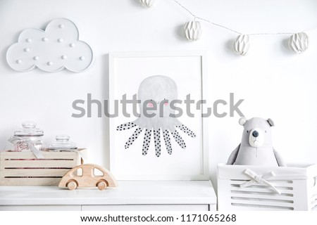 Stylish scandinavian newborn baby shelf with mock up photo frame,  box, teddy bear and toys. Modern interior with white walls and wooden accessories. Royalty-Free Stock Photo #1171065268