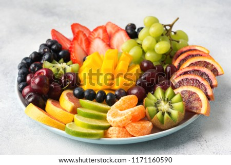 Raw fruits berries assortment platter on the white plate, on the off white table, selective focus #1171160590