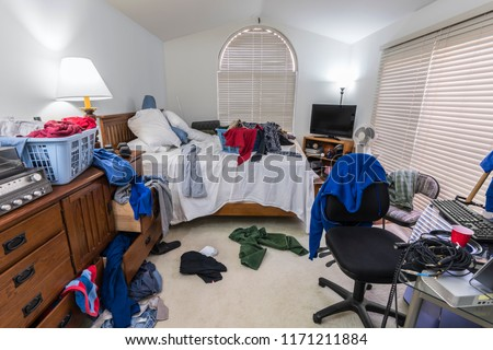 Messy, cluttered teenage boy's bedroom with piles of clothes, music and sports equipment.   #1171211884