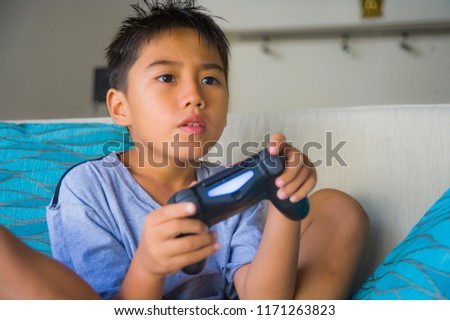 lifestyle portrait of Latin young child 8 years old excited and happy playing video game online holding remote controller enjoying having fun sitting on couch in internet gaming kid addiction #1171263823
