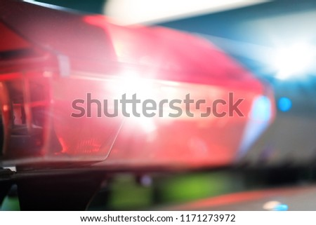 Red flashes on the car of the emergency vehicle at night. Police patrol car of the specialized unity in the night time. Police lights during traffic surveillance on the city road.