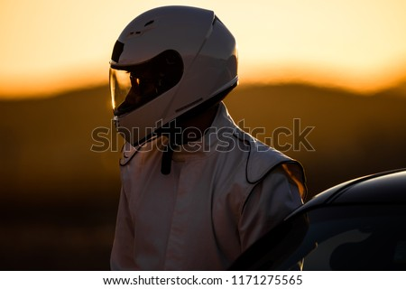 A Helmeted Race Car Driver At The Wheel #1171275565