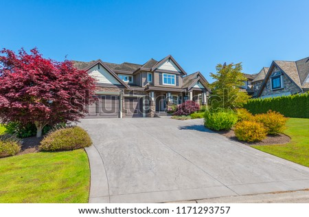 Big custom made luxury house with nicely landscaped and trimmed front yard and driveway to garage in the suburbs of Vancouver, Canada. #1171293757