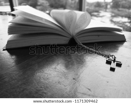Closeup view of Jesus christian cross necklace with blurred old book as background with selective focus, God concept picture with dark black and white for  monochrome process