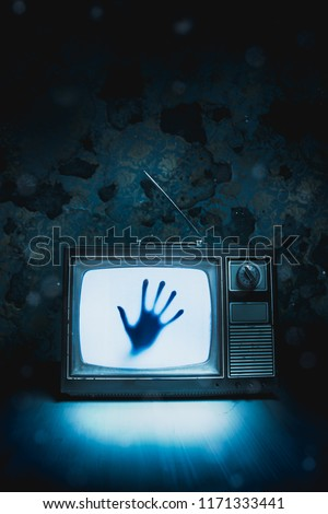 High contrast image of an old vintage TV with a hand inside Royalty-Free Stock Photo #1171333441