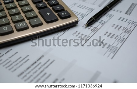 Calculator and black pen with accounting report and financial statement on desk. Accounting business concept.  #1171336924