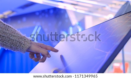 Woman using interactive touchscreen display with unrecognizable virtual map at modern technology show with futuristic interior #1171349965