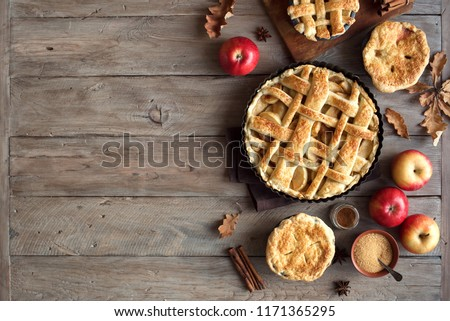 Homemade Apple Pies on rustic background, top view, copy space. Classic autumn Thanksgiving pastry dessert - organic apple pie. #1171365295