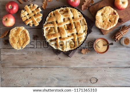Homemade Apple Pies on rustic background, top view, copy space. Classic autumn Thanksgiving dessert - organic apple pie. #1171365310