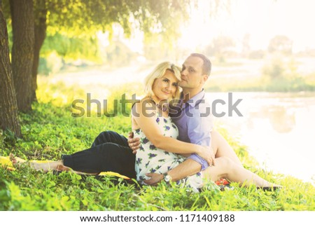 beautiful couple spends time romantically on the river bank at sunset in warm summer weather. the embrace of a man and a woman. I love #1171409188