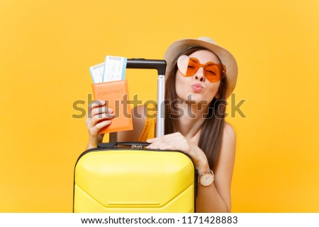 Fun tourist woman in summer casual clothes, hat, orange sunglasses with suitcase, passport isolated on yellow background. Passenger traveling abroad to travel on weekends getaway. Air flight concept #1171428883