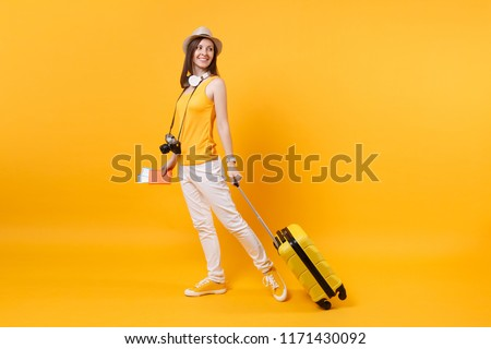 Traveler tourist woman in summer casual clothes, hat with headphones on neck isolated on yellow orange background. Passenger traveling abroad to travel on weekends getaway. Air flight journey concept #1171430092