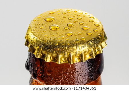 Bottle with soft drinks or alcohol in the ice. On gold caps and a bottle neck are drops of dew. Beer bottle cap close-up macro Isolated on white background with clipping path. #1171434361