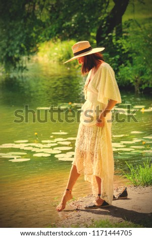 fashion and style. woman in a white dress and a summer straw hat stands on the shore of the pond and touches the water with her finger. retro style filter
